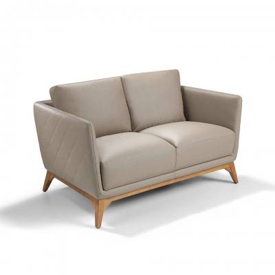 Sofá  tapizado en piel con patas de madera de Nogal